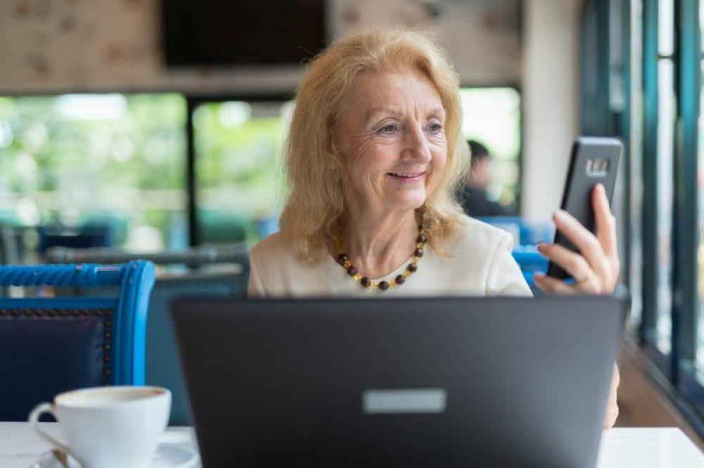 Äldre kvinna med telefon och laptop